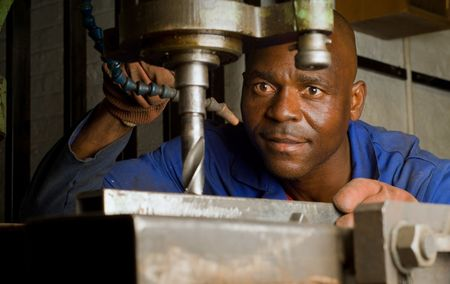 South African or American worker engineer working with industrial drill press