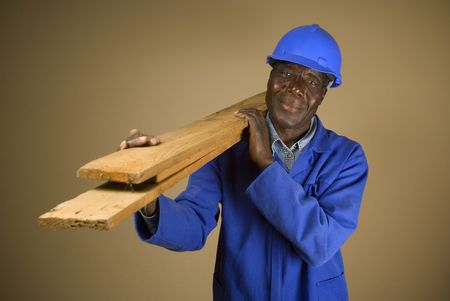 south african: Senior South African or American plumber, carpenter or builder with wooden planks