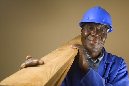Senior South African or American plumber, carpenter or builder with wooden planks photo