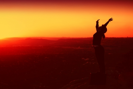 Silhouette of African American Business Woman ontop of Hill during Sunset Stock Photo