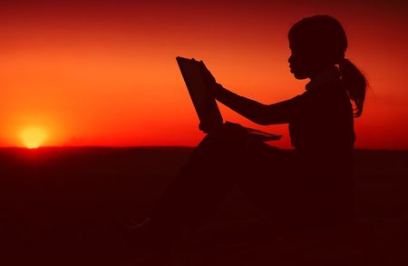 Silhouette of African American Business Woman Working with Laptop during Sunset ontop of a Hill photo