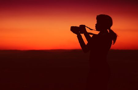 Silhouette of Business Woman with Binoculars Standing on a Hilltop photo