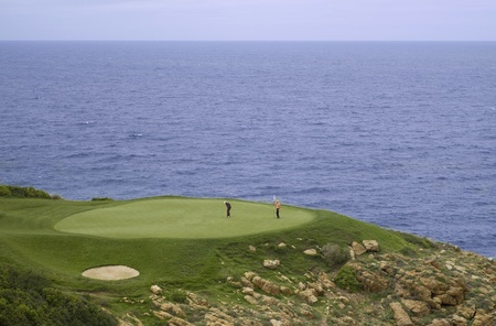 Perfect golf green hole at the sea