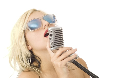Pretty woman or girl music singer with microphone and sunglasses on white photo