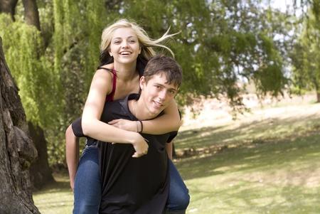 Happy girl on piggyback of boy friend in park photo