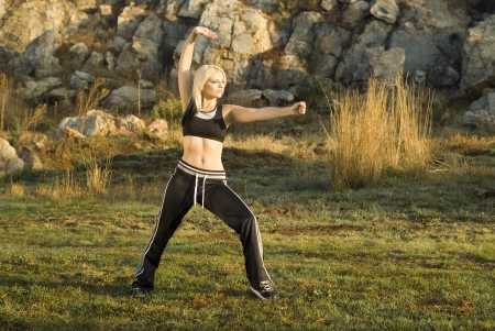 chi kung: Pretty woman praticing exercise tai chi, kung fu or yoga in natural park with gold light reflector Stock Photo
