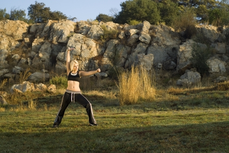 Pretty woman praticing exercise kung fu in natural park with gold light reflector photo