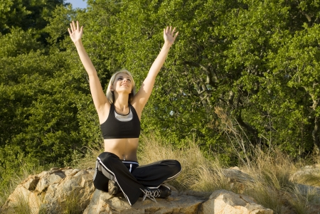 above head: Woman with hands above head in praise in park