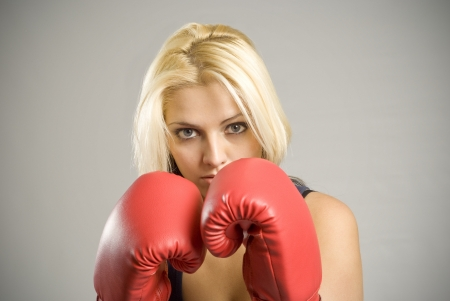 Portrait of pretty fit blond woman boxer training or working out with red boxing gloves photo