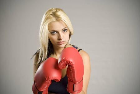 Fighting pretty fit blond woman boxer training or working out with red boxing gloves photo