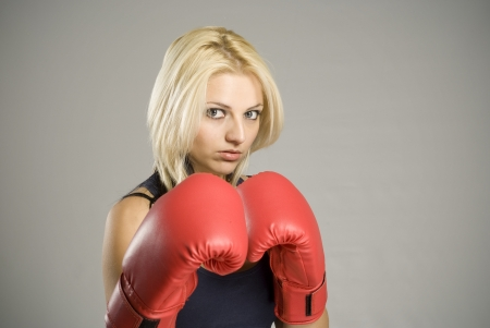 Boxing pose pretty fit blond woman boxer training or working out with red boxing gloves photo