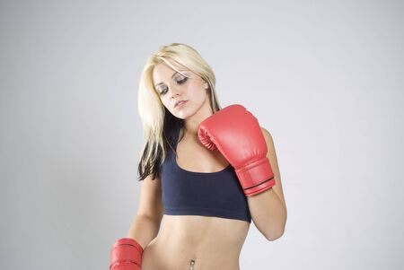 Elegant pose pretty fit blond woman boxer training or working out with red boxing gloves photo