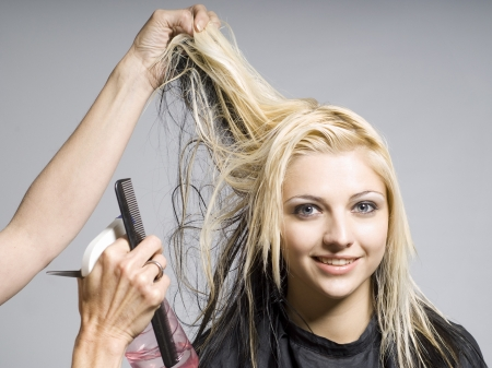 Hairdresser cutting hair of woman of smiling girl photo