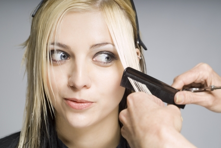 hair dresser: Client looking at comb whie hairdresser cutting hair