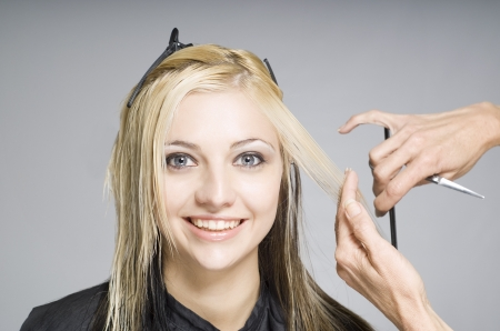 Smiling happy hair client or customer while hairdresser cutting hair Stock Photo