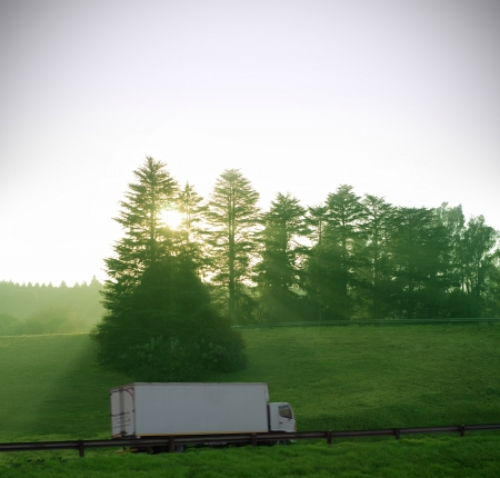 Sun and forest trees shine down on white truck delivery with motion blur on highway road