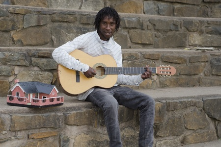 howick: African busker in Howick, KwaZulu-Natal with ethnic model house collecting money Stock Photo