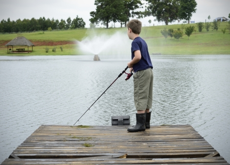 Boy bass fishing on dam or lake pier photo
