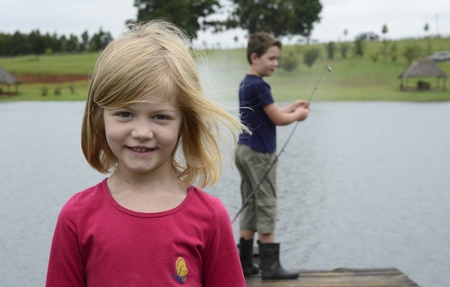 Young girl and boy fishing on wooden pier Stock Photo - 17161173