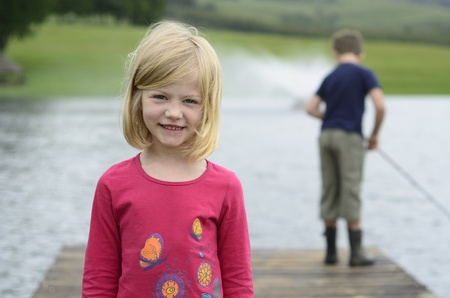 Young girl and boy fishing on wooden pier photo
