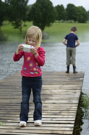 Young girl playing computer game in nature photo