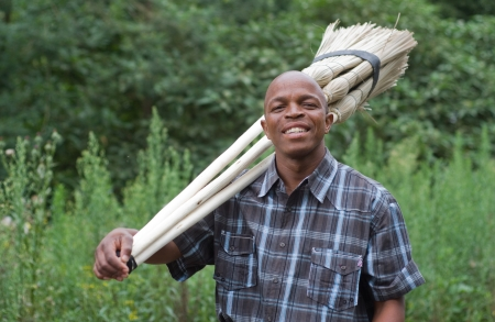 Stock photograph of a smiling black South African entrepreneur small business broom salesman in Hilton, Pietermaritzburg, Kwazulu-Natal photo