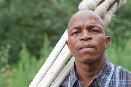 kwazulu natal: Stock photograph portrait of worred-looking a black South African entrepreneur small business broom salesman in Hilton, Pietermaritzburg, Kwazulu-Natal  Intentional limited depth of field with sharp focus on the eyes  Stock Photo