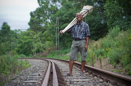 Stock photograph of a black South African entrepreneur small business broom salesman on railway line in Hilton, Pietermaritzburg, Kwazulu-Natal photo