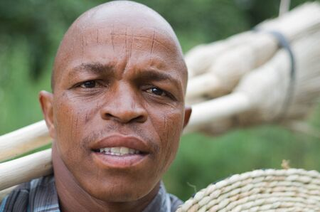 Stock photograph portrait of worred-looking a black South African entrepreneur small business broom salesman in Hilton, Pietermaritzburg, Kwazulu-Natal  Intentional limited depth of field with sharp focus on the eyes  photo