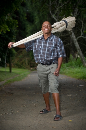 Stock photograph of a smiling black South African entrepreneur small business broom salesman in Hilton, Pietermaritzburg, Kwazulu-Natal photo