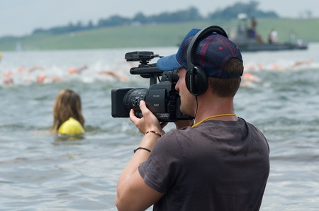 filming: MIDMAR DAM - 10 FEBRUARY 2013: An unidentified television cameraman films footage of the main event of the Midmar Mile near Howick, KwaZulu-Natal, South Africa Editorial