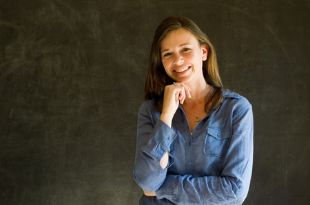 Confident woman with arms crossed against a blackboard background