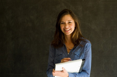 Confident woman with notepad and pen against a blackboard background