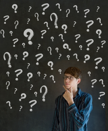 Thinking business man with chalk questions marks on blackboard background Stock Photo - 18455825