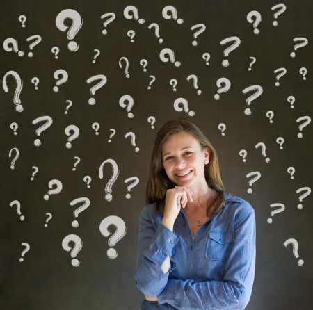 Thinking business woman with chalk questions marks on blackboard background photo