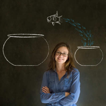 big and small: Business woman, student or teacher with fish jumping from small bowl to big bowl on blackboard background