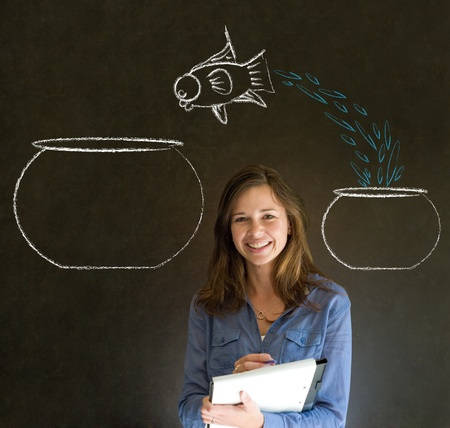 employee training: Business woman, student or teacher with fish jumping from small bowl to big bowl on blackboard background