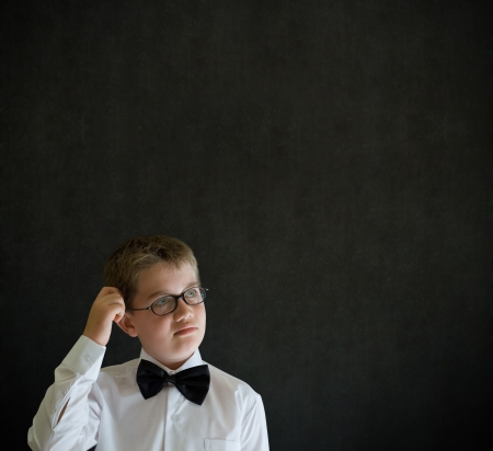 Scratching head thinking boy dressed up as business man, teacher or student on blackboard background photo