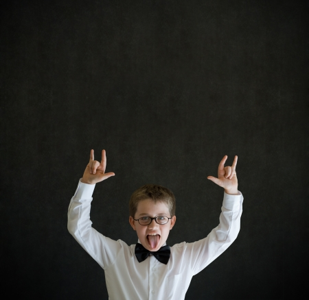 Education rocks boy dressed up as business man, teacher or school student pointing on blackboard background photo