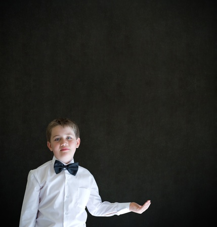 anything: Boy dressed up as businessman holding anything on cupped hand blackboard background