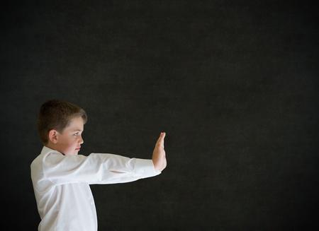niño empujando: Niño vestido como hombre de negocios, profesor o estudiante de empuje en el fondo pizarra Foto de archivo
