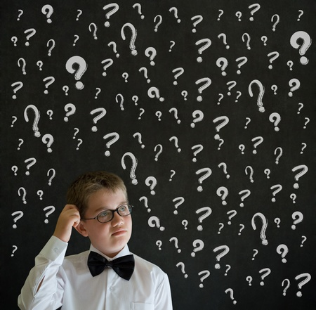 Scratching head thinking boy dressed up as business man with chalk questions marks on blackboard background photo