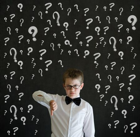 Thumbs down boy dressed up as business man with chalk questions marks on blackboard background photo