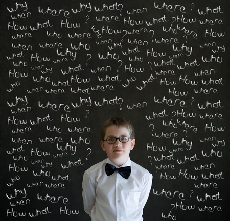 Thinking boy dressed up as business man with chalk questions on blackboard background photo
