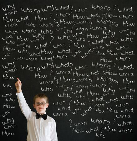 Hand up answer boy dressed up as business man with chalk questions on blackboard background Stock Photo - 19404455