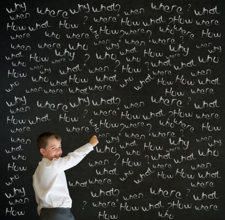 Writing boy dressed up as business man with chalk questions on blackboard background Standard-Bild