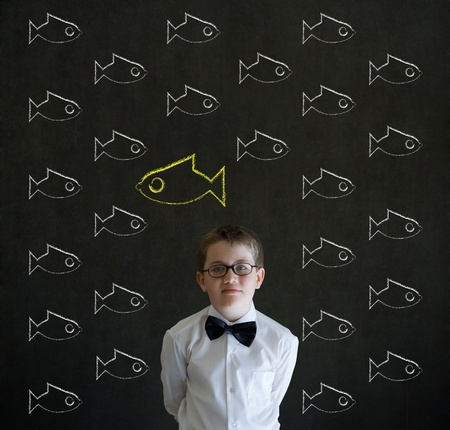 against the flow: Thinking boy dressed up as business man with independent thinking chalk fish swimming against the flow on blackboard background