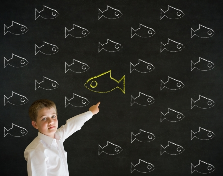 against the flow: Pointing boy dressed up as business man with independent thinking chalk fish swimming against the flow on blackboard background