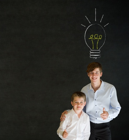 Thumbs up boy dressed up as business man with teacher man and bright idea chalk background lightbulb on blackboard background photo