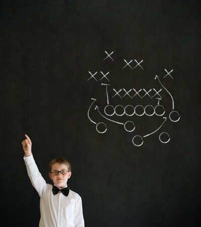 games hand: Hand up answer boy dressed up as business man with chalk American football strategy on blackboard background